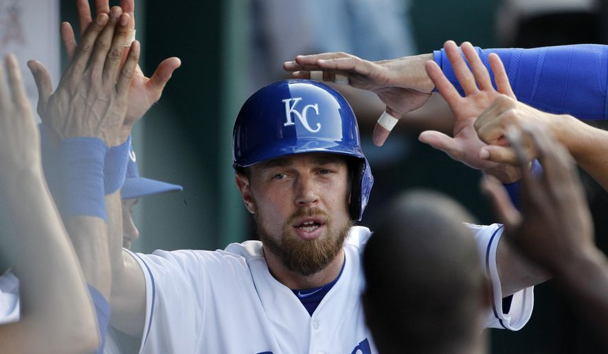 Kansas City Royals' Ben Zobrist is congratulated in the dugout after scoring on a Eric Hosmer single in the first inning of a baseball game against the Los Angeles Angels at Kauffman Stadium in Kansas City, Mo., Sunday, Aug. 16, 2015. (AP Photo/Colin E. Braley)