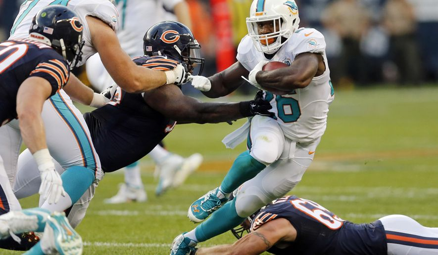 Miami Dolphins running back Lamar Miller, right,  cuts in front of Chicago Bears defensive tackle Ego Ferguson, middle, during the first half of an NFL preseason football game in Chicago, Thursday, Aug. 13, 2015. (AP Photo/Charles Rex Arbogast)