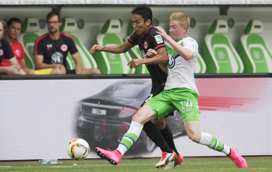 Wolfsburg's Kevin De Bruyne fouls Frankfurt's Makoto Hasebe during the German Bundesliga soccer match between VfL Wolfsburg and Eintracht Frankfurt in Wolfsburg, Germany, Sunday, Aug. 16, 2015.(AP Photo/Joerg Sarbach)
