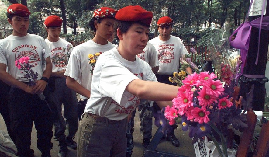 FILE - In this June 11, 1996 file photo, Guardian Angels from Tokyo place flowers at the site of a sexual assault of a woman the previous week in New York's Central Park. The Angels were in New York to meet with their New York counterparts. Guardian Angels volunteers recently made a pointed return to Central Park for the first time in over two decades. The anti-crime group says it felt compelled to resume nightly safety rounds in the iconic park because of a 28-percent rise in crime there so far this year. (AP Photo/Mark Lennihan, File)