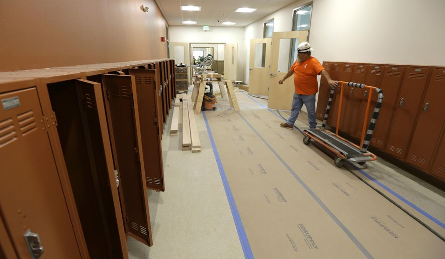 In this July 13, 2015 photo, Jerry Kellogg of Master Millwork wheels a lumber cart past open lockers in a hallway of the Destiny Charter Middle School in Tacoma, Wash. The school, which will open in the fall, will start with 200 students in the sixth grade and will be one of nine charter schools operating in the state of Washington during the upcoming school year. (AP Photo/Ted S. Warren)