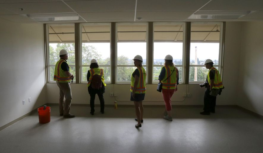 In this July 13, 2015 photo, visitors wearing safety vests and hard hats look out a window during a tour of the Destiny Charter Middle School in Tacoma, Wash. The school, which will open in the fall, will start with 200 students in the sixth grade. The school will be one of nine charter schools operating in the state of Washington during the upcoming school year. (AP Photo/Ted S. Warren)