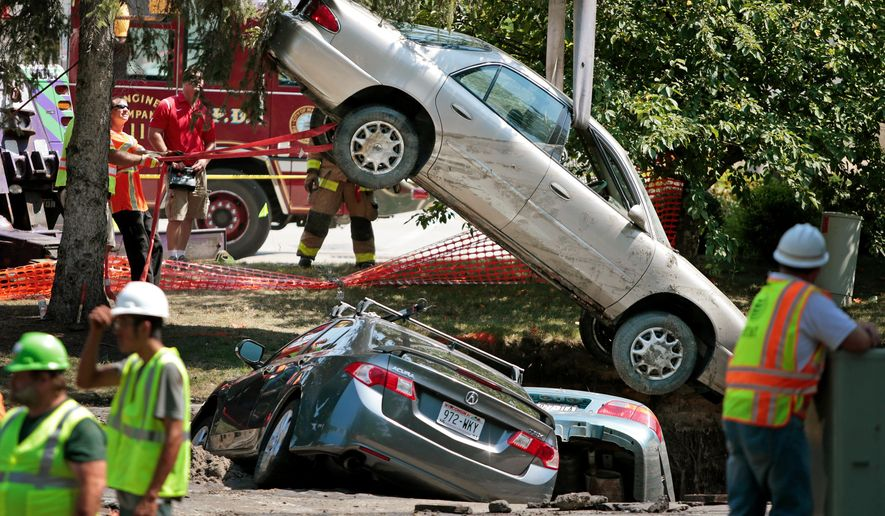Towing company workers lift one of three cars out of a sinkhole in the parking lot of an apartment complex, Friday, Aug. 14, 2015, in Madison, Wis. About 300 residents of the complex were evacuated after a water pipe break created the sinkhole and potential gas leak. (Michael P. King/Wisconsin State Journal via AP) MANDATORY CREDIT