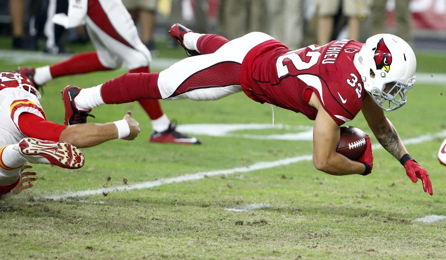Arizona Cardinals free safety Tyrann Mathieu (32) is tripped up by Kansas City Chiefs quarterback Alex Smith (11) after intercepting a pass by Smith during the first half of an NFL preseason football game, Saturday, Aug. 15, 2015, in Glendale, Ariz. (AP Photo/Ross D. Franklin)
