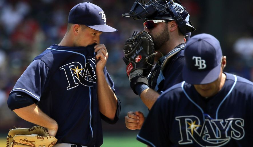Tampa Bay Rays starting pitcher Drew Smyly, left, confers with catcher Curt Casali, center, after a visit to the mound by pitching coach Jim Hickey, right, during the fourth inning of a baseball game against the Texas Rangers in Arlington, Texas, Sunday, Aug. 16, 2015. (AP Photo/LM Otero)