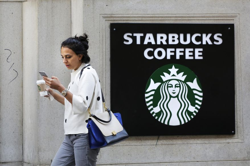 FILE- In this July 16, 2015, file photo, a woman walks out of a Starbucks Coffee with a beverage in hand in New York. Starbucks and Panera are each hyping reformulated versions of their pumpkin spice lattes in a fight to win over fans of the drink in coming weeks. Starbucks Corp. said Monday, Aug. 17, its version of the concoction this year will be made with real pumpkin, and without caramel coloring. (AP Photo/Mark Lennihan, File)