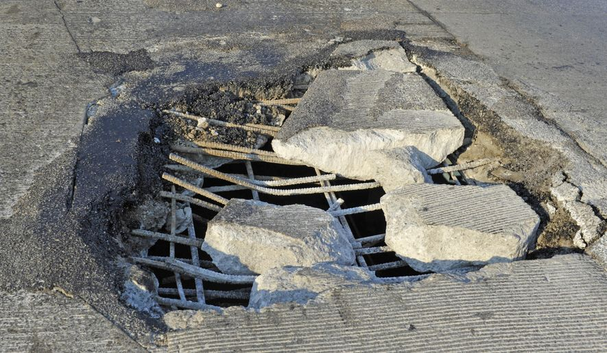 Two large, nearly side by side holes on northbound Interstate 75 on the Rouge Overpass have sidelined a number of cars, causing a massive traffic jam on the freeway in Detroit, Mich., on Monday Aug. 17, 2015.  Officials say potholes are to blame for snarling traffic and damaging a number of vehicles during the morning commute in Detroit.  (Charles V. Tines/The Detroit News via AP)