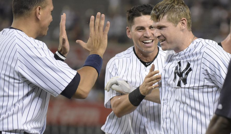 New York Yankees' Chase Headley, right, celebrates with Jacoby Ellsbury and Alex Rodriguez, left, after the winning run scored as Headley grounded out with bases loaded during the 10th inning of a baseball game against the Minnesota Twins Monday, Aug 17, 2015, at Yankee Stadium in New York. The Yankees won 8-7. (AP Photo/Bill Kostroun)