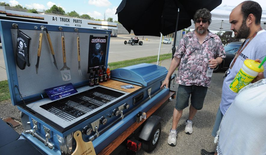 """Nightmare Cruisers hearse club president Steve Frey, left, shows off his """"Open Casket Bar and Grill"""" to Mackinley and Erika Watson, of Pontiac, Mich., during the inaugural Scream Cruise on Sunday, Aug. 16, 2015. Hosted by the Nightmare Cruisers Hearse Club, the inaugural Scream Cruise screeched into Pontiac, with its collection of funeral coaches, skull-mobiles, rat rods and motorcycles. (Brandy Baker/The Detroit News via AP)"""