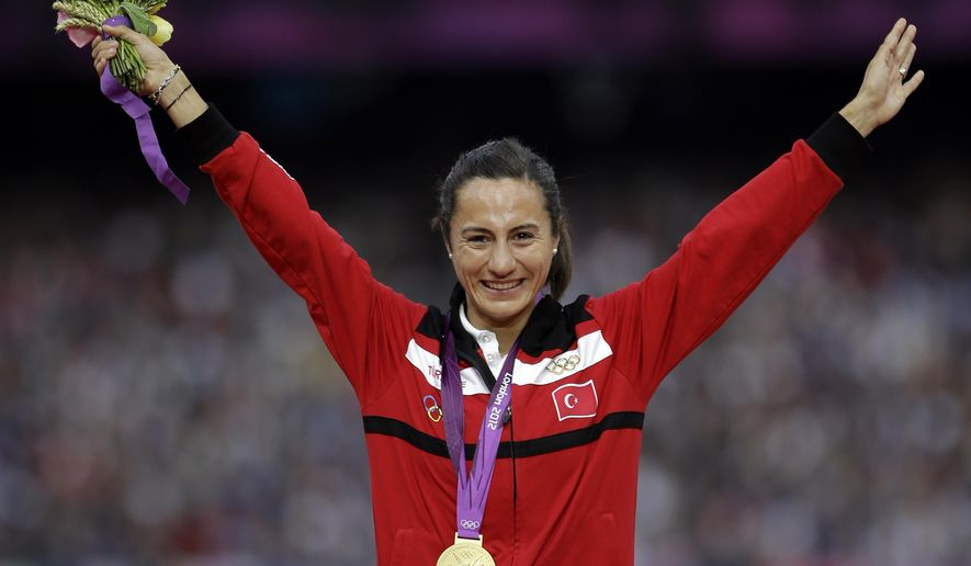 FILE - In this Aug. 11, 2012 file photo Turkey's Asli Cakir Alptekin poses with her gold medal for the women's 1500-meter during the athletics in the Olympic Stadium at the 2012 Summer Olympics, London. Olympic 1,500 meters champion Asli Cakir Alptekin of Turkey has agreed to give up her title and serve an 8-year ban for blood doping. The Court of Arbitration for Sport said Monday, Aug. 17, 2015 it approved a settlement agreed by Alptekin and the IAAF.  (AP Photo/Matt Slocum, file)