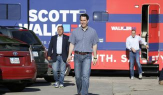 In this July 31, 2015, file photo, Republican presidential candidate Wisconsin Gov. Scott Walker walks from his campaign bus to meet with local residents at Tom and Tiff's diner, in Glenwood, Iowa. (AP Photo/Charlie Neibergall, File) ** FILE **