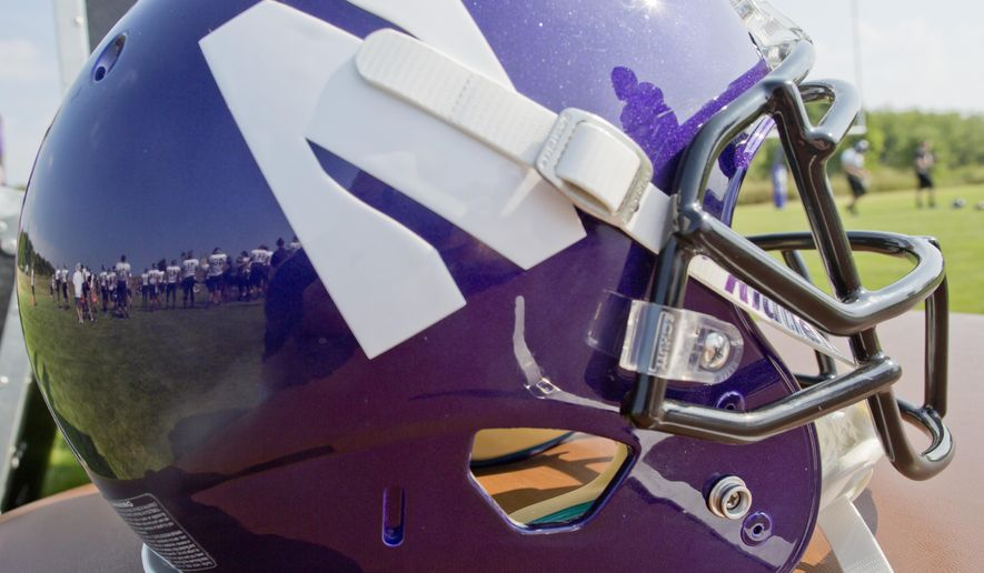 Northwestern football players are reflected in a helmet during drills at practice at the University of Wisconsin-Parkside campus on Monday, Aug. 17, 2015, in Kenosha, Wi. (AP Photo/Jeffrey Phelps)