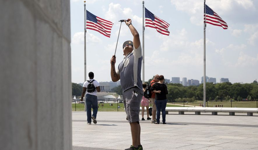 Octavio Flores, a tourist from Miami, photographs the Washington Monument on the National Mall in Washington Monday, Aug. 17, 2015. Tourism officials say Washington drew a record 20.2 million visitors last year, with increases in international and domestic visitors. The Lincoln Memorial is in the background. (AP Photo/Carolyn Kaster)