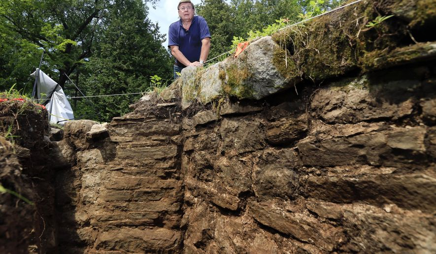 Archaeologist David Starbuck poses near a stone wall unearthed at Lake George Battlefield Park on Monday, Aug. 17, 2015, in Lake George, N.Y. An archaeological dig at the 18th-century military site in the southern Adirondacks has uncovered large sections of stone walls that are believed to have been constructed within a larger British fortification that was never completed more than 250 years ago. (AP Photo/Mike Groll)