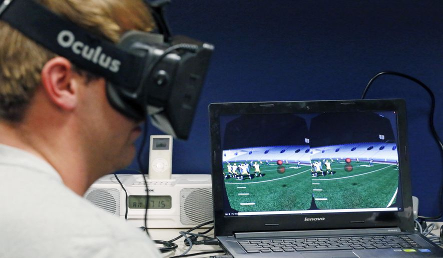 In this July 27, 2015 photo, Mississippi quarterback Ryan Buchanan uses a virtual reality headset to make football play decisions at the Manning Center in Oxford, Miss. Ole Miss is one of a growing number of football programs in the NCAA and NFL dabbling in virtual reality technology to help supplement work on the field. (AP Photo/Rogelio V. Solis)