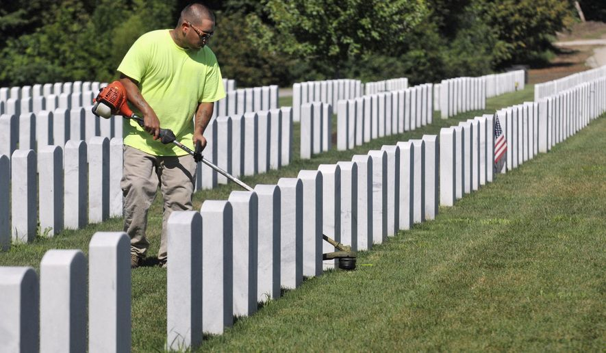 In this Aug. 12, 2015 photo, Luis Valenzuela, of Gateway To Outdoor Solutions, trims the grass around headstones at the Rock Island National Cemetery at Rock Island Arsenal, Ill. Officials at the cemetery in Western Illinois say they believe many veterans and their family members who could qualify aren't taking advantage of free burials. (Gary Krambeck/The Dispatch via AP)