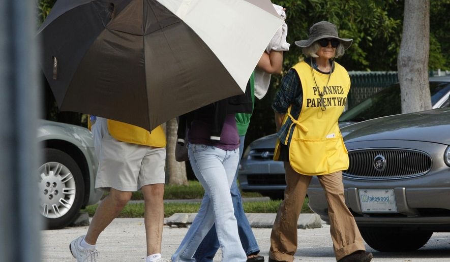 In this Sept. 14, 2009, file photo, women are concealed from view by Planned Parenthood volunteers as they enter the Planned Parenthood of Collier County in Naples, Fla. Planned Parenthood in Florida asked a judge Monday, Aug. 17, 2015, for an emergency ruling to allow them to continue performing abortions at 12 and 13 weeks after a discrepancy with the state about what constitutes first and second-trimester abortions. (David Albers/Naples Daily News via AP, File)