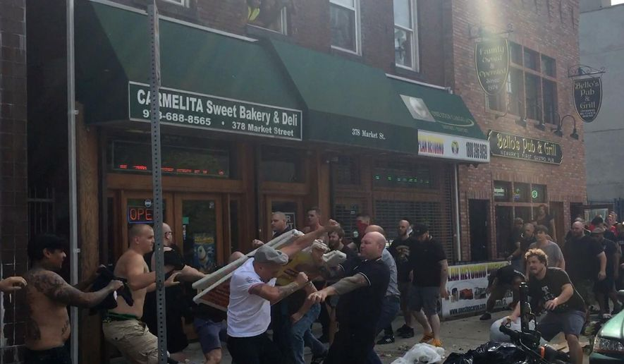 In this image made from video taken on Sunday, Aug. 9, 2015, soccer supporters skirmish outside a pub ahead the Major League Soccer derby between the New York Bulls and New York City FC, in Newark, New Jersey. Rivalries can take years, often decades, to develop in world sport. Not so in the United States, where an established team can find itself with a local challenger almost overnight as enough cash and ambition can buy an immediate ticket to the top division. (AP Photo/Rob Harris)