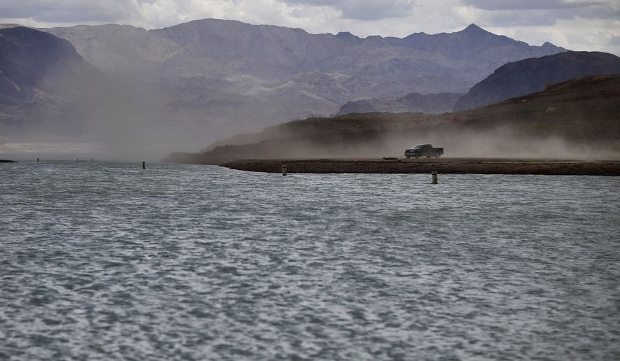 FILE - In this Monday, May 18, 2015 photo, wind kicks up dust on an area that was once underwater at the Boulder Harbor boat ramp in the Lake Mead National Recreation Area,  near Boulder City, Nev. Wet weather in May and June prompted optimistic projections Monday, Aug. 17, 2015 from federal water managers keeping close tabs on the Colorado River water supply for about 40 million residents in seven Southwest U.S. states. The West remains in a historic drought, and Lake Mead right now is just 38 percent full. (AP Photo/John Locher, File)