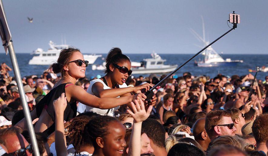 People use selfie sticks during the Maroon 5 beach concert in Atlantic City, NJ,  Sunday, Aug. 16 2015. (Ben Fogletto/The Press of Atlantic City via AP)