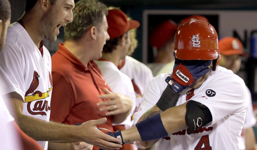 St. Louis Cardinals' Yadier Molina, right, covers his face as he is congratulated by teammate Michael Wacha after hitting a solo home run during the fourth inning of a baseball game against the San Francisco Giants Monday, Aug. 17, 2015, in St. Louis. (AP Photo/Jeff Roberson)