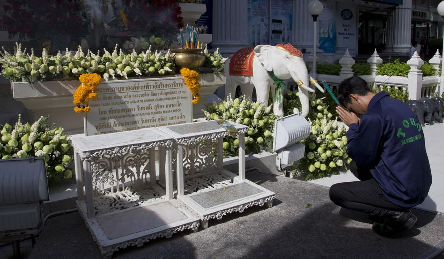 A man prayers near the Erawan Shrine the morning after an explosion in Bangkok, Thailand, Tuesday, Aug. 18, 2015. A bomb exploded Monday within a central Bangkok shrine that is among the city's most popular tourist spots, killing a number of people and injuring others, police said. (AP Photo/Mark Baker)