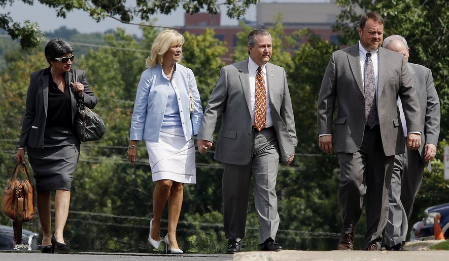 Mike Hubbard, center, walks to the Lee County Justice Center for a hearing holding hands with his wife Susan Hubbard, Monday, Aug. 17, 2015 in Opelika, Ala. Circuit Judge Jacob Walker tentatively pushed back Hubbard's ethics trial until a date in March that overlaps with the 2016 legislative session. Hubbard faces 23 felony ethics counts accusing him of using his public offices to enrich his businesses. (Todd J. Van Emst/Opelika-Auburn News via AP)