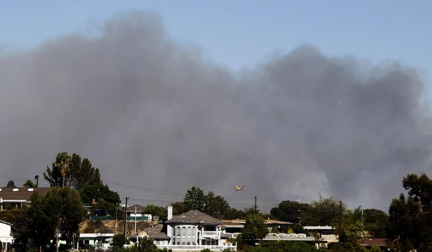 A water-dropping aircraft flies in Monterey Park, Calif., Sunday, Aug. 16, 2015, towards a fire near Glendora, Calif. in the Angeles National Forest. The fire that broke out in northern Los Angeles County has burned several structures. (AP Photo/Nick Ut)