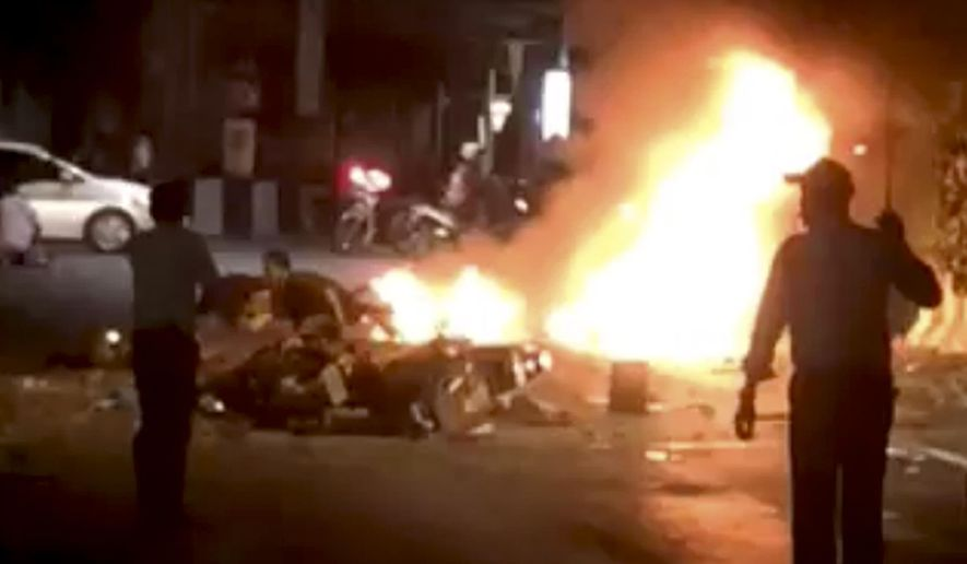 In this image provided by Mongkol Nunthalikitkun flames burn after an explosion in Bangkok, Monday, Aug. 17, 2015. A large explosion rocked a central Bangkok intersection during the evening rush hour, killing a number of people and injuring others, police said. (Mongkol Nunthalikitkun via AP)