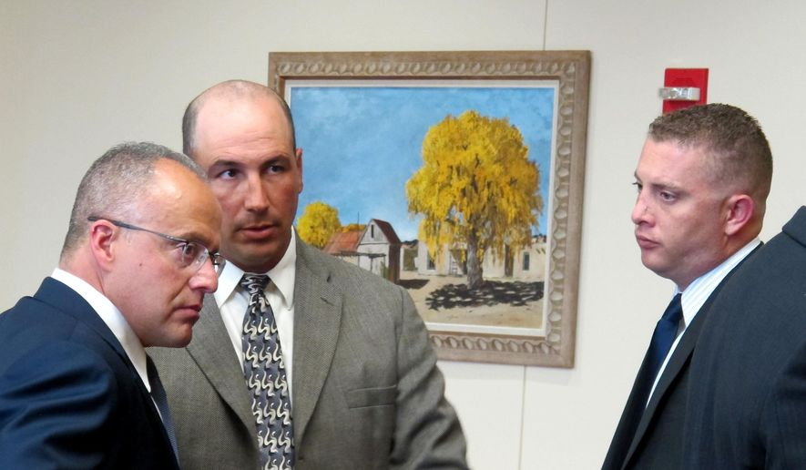 Defense attorney Luis Robles, left, talks to former Albuquerque detective Keith Sandy, center, and Albuquerque officer Dominique Perez, right, during a preliminary hearing in Albuquerque, N.M. on Monday, Aug. 17, 2015. A judge is listening to testimony and will decide if Sandy and Perez should stand trial for the fatal shooting of a homeless man in 2014. (AP Photo/Russell Contreras)
