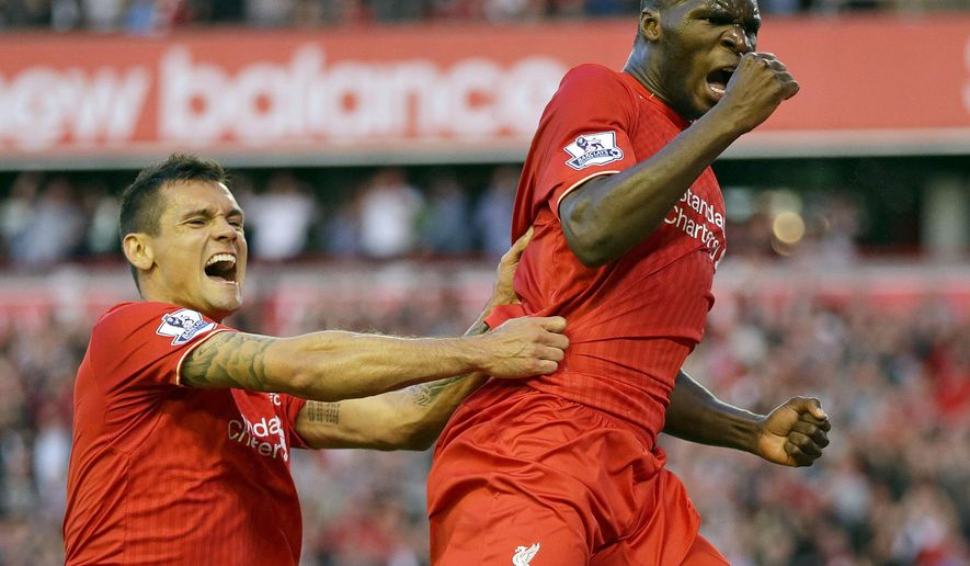 Liverpool's Christian Benteke right, celebrates with team-mate Dejan Lovren after he scores the first goal for his side during their English Premier League soccer match against Bournemouth at Anfield in Liverpool, England, Monday Aug. 17, 2015. (AP Photo/Clint Hughes)
