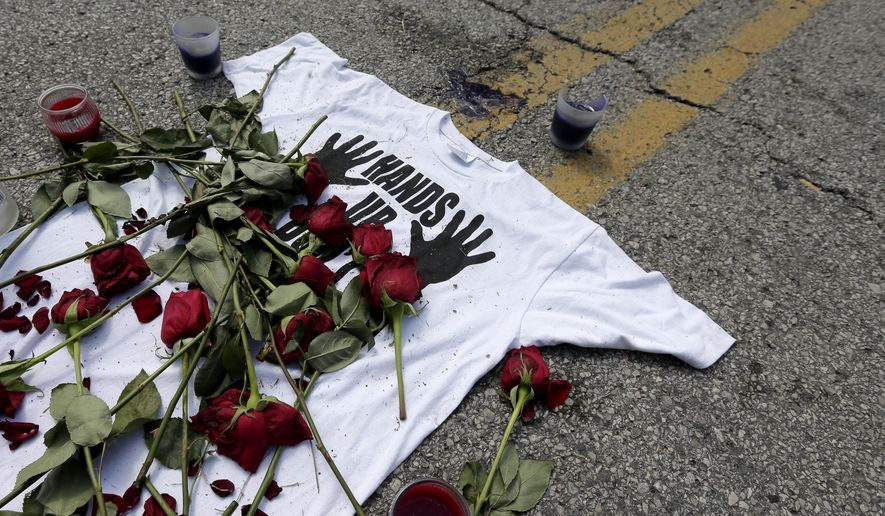 "FILE- In this Aug. 19, 2014 photo, a shirt reading ""hands up don't shoot"" is covered with roses at the spot Michael Brown was killed by police Aug. 9 in Ferguson, Mo. A member of the grand jury that declined to indict a white Ferguson police officer in Brown's  shooting death is challenging a federal judge's dismissal of her lawsuit that sought to allow her to speak publicly about those secret proceedings. A hearing is scheduled for Tuesday, Aug. 18, 2015. (AP Photo/Charlie Riedel, File)"