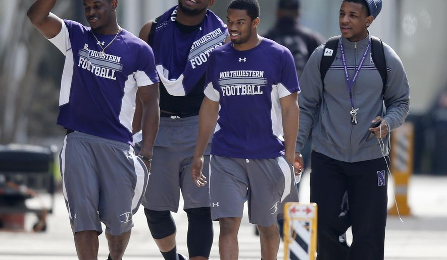 FILE - In this April 25, 2014, file photo, unidentified Northwestern football players walk between their locker room and McGaw Hall, where voting is taking place on the student athlete union question, in Evanston, Ill. The National Labor Relations Board has dismissed a historic ruling that Northwestern University football players are school employees who are entitled to form what would be the nation's first union of college athletes. The NLRB released its decision Monday, Aug. 17, 2015. The losing side does not have an option to appeal. (AP Photo/Charles Rex Arbogast, File)