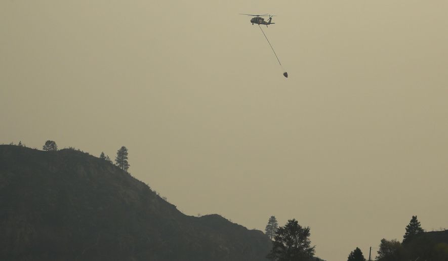 A helicopter used for fighting wildfires carries a water bucket above a burned ridge line above the Columbia river, Monday, Aug. 17, 2015, outside of Chelan, Wash. Big wildfires threatened the Lake Chelan resort region of central Washington on Monday after driving away tourists, destroying a warehouse filled with nearly 2 million pounds of apples and forcing thousands of residents to flee. (AP Photo/Ted S. Warren)