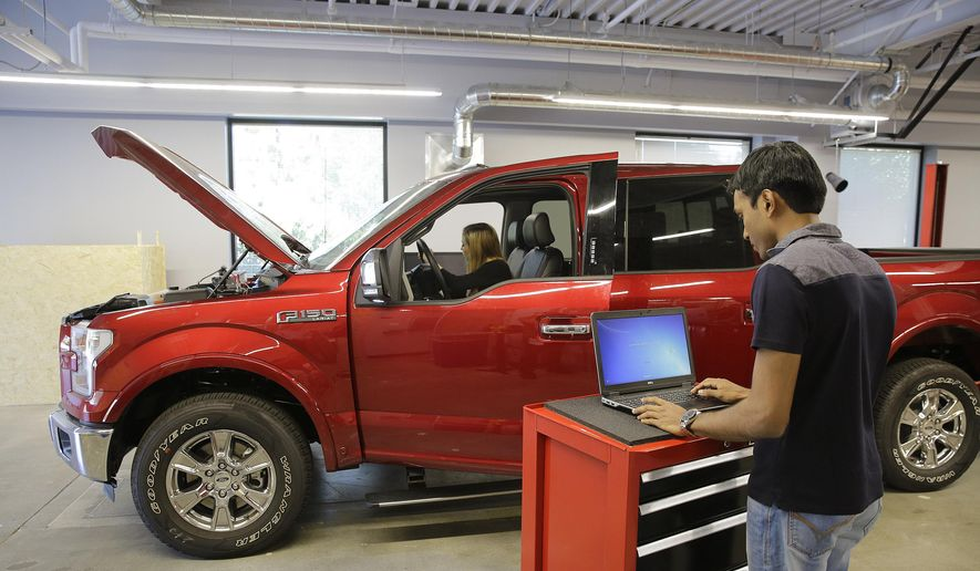 In this photo taken Thursday, Aug. 13, 2015, Nitin Bandaru, right, works on a hackathon project at the Ford Motor Company Research and Innovation Center in Palo Alto, Calif. (AP Photo/Eric Risberg) ** FILE **
