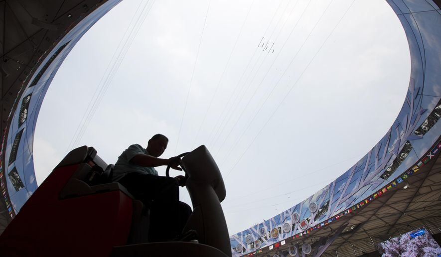 A worker uses a machine to clean the track at the iconic Bird's Nest National Stadium as preparation for the upcoming 15th IAAF Athletics World Championship in Beijing Tuesday, Aug. 18, 2015. The sport event will be held in Beijing from Aug. 22 to 30. (AP Photo/Andy Wong)