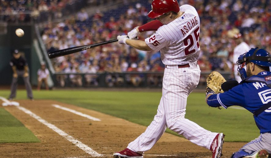 Philadelphia Phillies' Cody Asche (25) hits a single during the fourth inning of a baseball game against the Toronto Blue Jays, allowing Odubel Herrera to score, Tuesday, Aug. 18, 2015, in Philadelphia. (AP Photo/Laurence Kesterson)