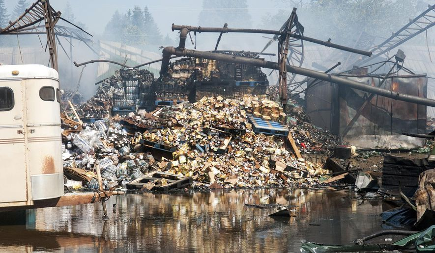 Remnants spill into a creek from a warehouse full of food products that was destroyed in an early-morning fire on Tuesday, Aug. 18, 2015, Winlock, Wash. The fire caused vegetable oil to leak into nearby Olequa Creek and a spokesman for the Washington Department of Ecology feared the spill might have killed thousands of small salmon and other fish. (Natalie Johnson/The Chronicle via AP) MANDATORY CREDIT