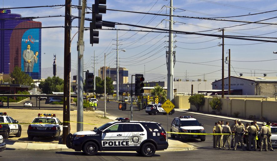Metro officers gather along W. Harmon Ave. after a pair of propane tanks exploded outside of Vegas Balloon Rides west of the Las Vegas Strip on Tuesday, Aug. 18, 2015, leaving a 35-year-old man hospitalized with burns to his arm and leg. A spokesman for Vegas Balloon Rides said Tuesday that a pilot was refueling balloon tanks when the blast occurred. Jeff Chatterton says on-site refueling is routine and the company isn't sure which tanks sparked the fire.  (L.E. Baskow/Las Vegas Sun via AP)
