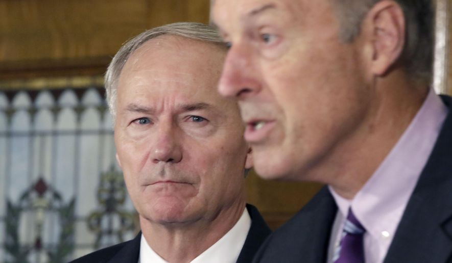 Arkansas Gov. Asa Hutchinson, left, listens as John Selig, director of the Arkansas Department of Human Services speaks during a news conference at the Arkansas state Capitol in Little Rock, Ark., Tuesday, Aug. 18, 2015. Hutchinson said the state will resume its push to terminate Medicaid coverage for thousands of people, despite complaints that many being kicked off the program still qualify. (AP Photo/Danny Johnston)