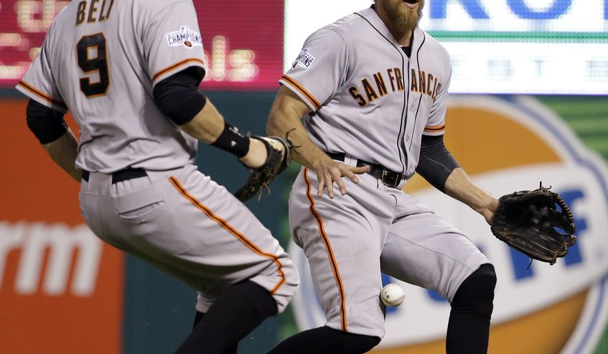 San Francisco Giants right fielder Hunter Pence, right, and first baseman Brandon Belt can't reach a foul ball hit by St. Louis Cardinals' Michael Wacha during the third inning of a baseball game Monday, Aug. 17, 2015, in St. Louis. (AP Photo/Jeff Roberson)