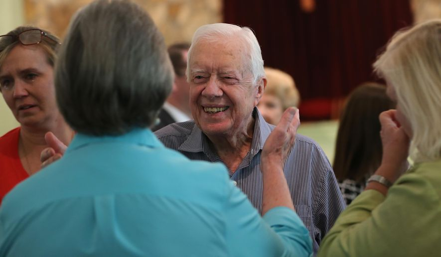 Former President Jimmy Carter reaches to embrace his brother Billy's widow Sybil while greeting family Sunday, Aug. 16, 2015, following service at Maranatha Baptist Church in Plains, Ga. Carter's nieces Mandy Flynn, left, and Jana Carter are also pictured. Sunday at church was emotional because it was the first time many members had seen Carter since his announcement that he has cancer. (Ben Gray/Atlanta Journal-Constitution via AP)