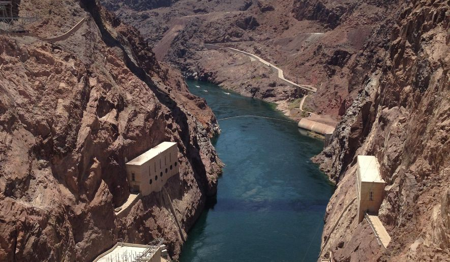 This July 18, 2014 photo shows a view from the Hoover Dam on the Arizona-Nevada border looking toward the O'Callaghan-Tillman Memorial Bridge. The dam is considered a civil engineering wonder. It's located about 30 minutes from Las Vegas and is a top destination in the region. (AP Photo/John Marshall)