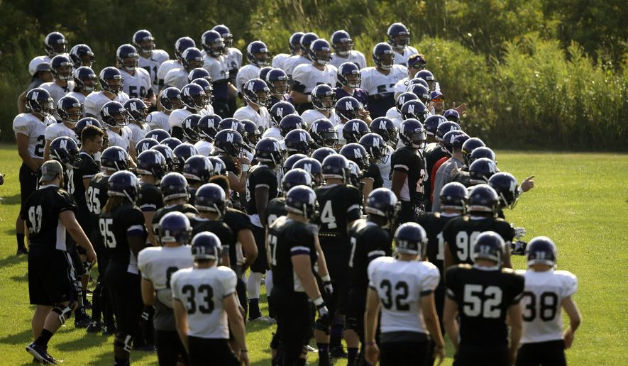 Northwestern football players gather during practice at the University of Wisconsin-Parkside campus on Monday, Aug. 17, 2015, in Kenosha, Wi. The National Labor Relations Board on Monday, Aug. 17, 2015, overturned a historic ruling that gave Northwestern University football players the go-ahead to form the nation's first college athletes' union, saying the prospect of union and non-union teams could throw off the competitive balance in college football. (AP Photo/Jeffrey Phelps)