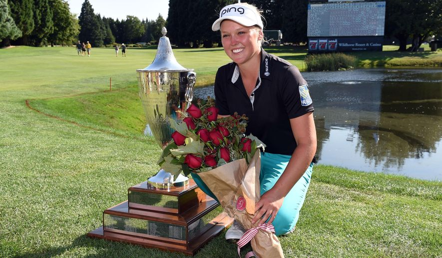 Brooke M. Henderson, of Canada, poses with the trophy on the 18th hole after winning the Cambia Portland Classic golf tournament in Portland, Ore., Sunday, Aug. 16, 2015. (AP Photo/Steve Dykes)