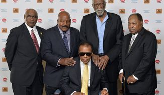 Back Row, from left, John Wooten, Jim Brown, Bill Russell, and Bobby Mitchell stand behind Muhammad Ali before the start of the Ali Humanitarian Awards ceremony Saturday, Sept. 27, 2014 at the Louisville Mariott Downtown in Louisville, Ky. The four were participants of the 'Ali Summit' in 1967, and Brown will be receiving the Ali Humanitarian Lifetime Achievement Award. (AP Photo/Timothy D. Easley)