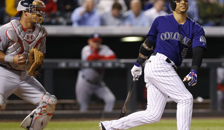 Colorado Rockies' Carlos Gonzalez, right, reacts after striking out in front of Washington Nationals catcher Wilson Ramos during the fifth inning of a baseball game Tuesday, Aug. 18, 2015, in Denver. (AP Photo/David Zalubowski)