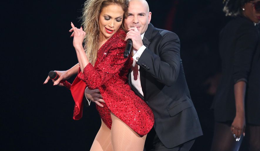 FILE - In this Nov. 23, 2014 file photo, Jennifer Lopez, left, is embraced by Pitbull at the end of her performance at the 42nd annual American Music Awards in Los Angeles. Lopez and Pitbull will headline the iHeartRadio Fiesta Latina concert in Miami this November, which will be streamed live online. The Nov. 7 event will be streamed live on Yahoo Live. Telemundo and iHeartMedia Spanish-language stations will also broadcast the event. Tickets go on sale to the general public on Saturday. (Photo by Matt Sayles/Invision/AP, File)
