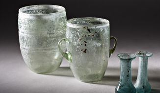 This handout photo provided by the Israel Antiquities Authority (IAA) shows glass vessels, Burial Tomb cave Akeldama, Jerusalem, early Roman Period. The Museum of the Bible, now under construction in Washington, will feature ancient artifacts and treasures from the Holy Land under a new deal with the Israel Antiquities Authority. (Israel Antiquities Authority/Meidad Suchowolski via AP)