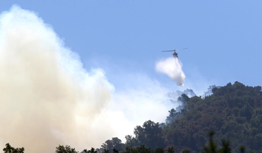 Helicopter drops water above Highway 101 on Cuesta Grade, the Cuesta Fire Monday, Aug. 17, 2015, east of Santa Margarita, Calif. Crews worked to protect more than 300 homes from the wildfire on California's Central Coast, as the wind-whipped blaze exploded in size Tuesday, officials said. (David Middlecamp/The Tribune (of San Luis Obispo) via AP) MANDATORY CREDIT
